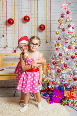 six years: Two funny sisters four girls and six years of playing and having fun in the home New Years interior Stock Photo