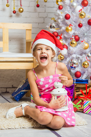 six year old: Six year old girl sitting on a mat at a snowy Christmas trees