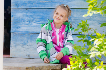 six year old: Six year old girl sitting on the porch of a wooden house and smiling happily Stock Photo