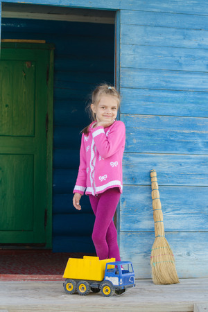 six year old: Six year old girl playing with toy dump truck on the porch of a wooden house