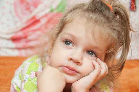 three year old: Cheerful three year old girl lying on the bed and looked to the left
