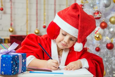 dwarf costume: Four-year girl dressed in a red suit Santa Claus draws pencils are in a festive Christmas interior Stock Photo