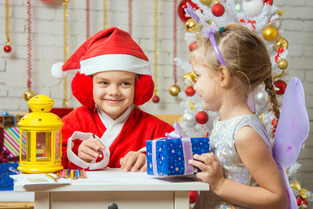 dwarf costume: A girl dressed in a red suit Santa Claus draws pencils sitting at the table, next is a girl dressed as a fairy with the candlestick