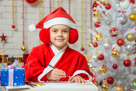 dwarf costume: Six year old girl dressed in a red suit Santa Claus draws pencils are in a festive Christmas interior Stock Photo