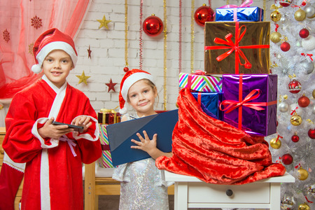 six years: Two girls sisters four and six years in the New Year costumes are at the bag with Christmas gifts Stock Photo