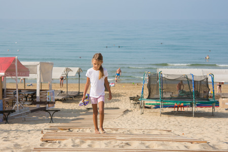 six year old: Six year old girl walking on wooden flooring in the sand from the sea back home