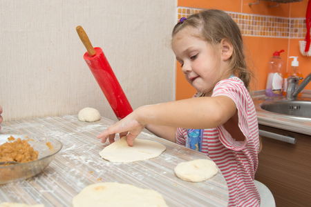 helps: Four-year girl prepares pies with cabbage in the kitchen Stock Photo