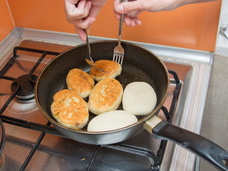 turns: The hostess turns two forks preparing fried patty in the pan Stock Photo