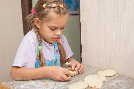 smeared baby: Four-year girl prepares pies with cabbage in the kitchen Stock Photo