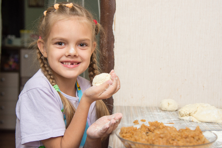 smeared baby: Cheerful girl stained with flour made patty with cabbage