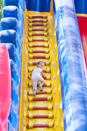 three year old: Three year old girl climbs on a big inflatable trampoline