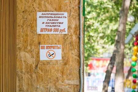 crossed cigarette: Two ads on the wall Use a lawn as a toilet-smoking and no smoking sign with a crossed-out cigarette Stock Photo