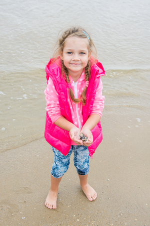 gather: Three year old girl standing with shells in her hand, which gather up on the beach