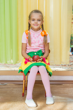 children clothing: Six year old girl sitting on a chair and holding an apple in his hand on a matinee in kindergarten