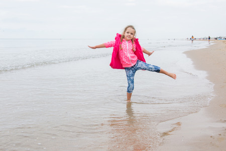 raises: Three year old girl having fun stood on one leg on the beach in the cool overcast weather Stock Photo