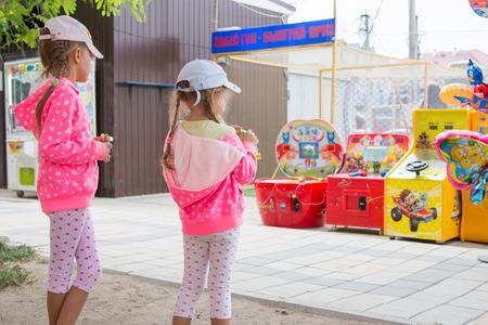 slot machines: Anapa, Rusia - 14 de septiembre de 2015: Dos niñas que come el chocolate con el interés que mira en las máquinas tragamonedas para niños