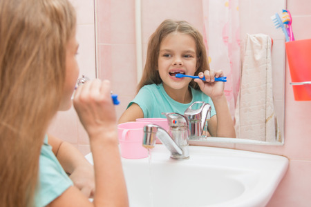 lower teeth: Six year old girl cleans the lower front teeth look in the mirror in the bathroom Stock Photo
