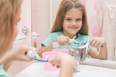 six year old: Six year old girl squeezes the toothpaste from a tube on toothbrush