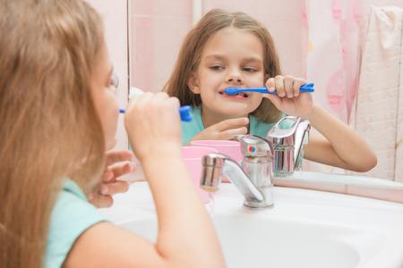 six year old: Six year old girl having fun brushing his teeth look in the mirror in the bathroom