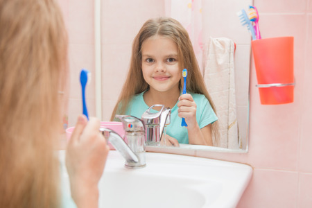 six year old: Six year old girl opening her mouth treats teeth in reflection in a mirror, while in the bathroom