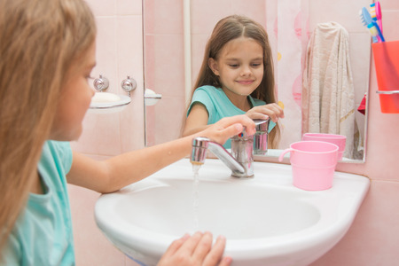 water flowing: Girl closes after washing the mixer tap in the bathroom Stock Photo