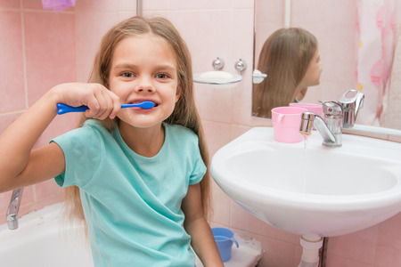 six year old: Six year old girl brushing her teeth and turned away from the sink looks in the picture Stock Photo