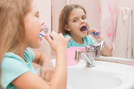 six year old: Six year old girl cleans the lower lateral teeth look in the mirror in the bathroom