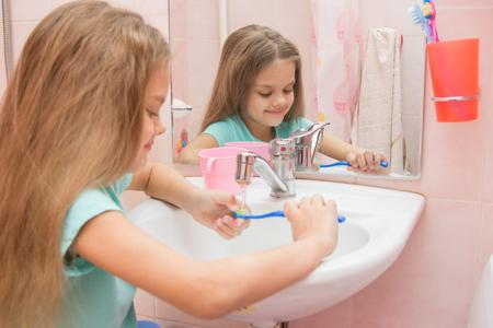 rinse: Girl rinse the toothbrush under running tap water Stock Photo