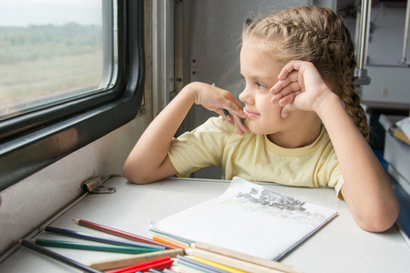 six year old: Six year old girl draws a pencil in a notebook for a side table in the second-class train carriage Stock Photo