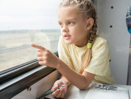 side table: Six year old girl draws a pencil in a notebook for a side table in the second-class train carriage Stock Photo