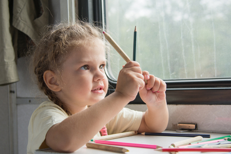side table: Four-year girl draws pencil in a notebook for a side table in the second-class train carriage