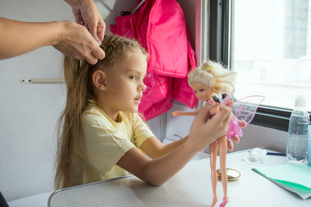 six year old: Six year old girl playing in the doll while mom pigtail braids of hair, in the second-class train carriage