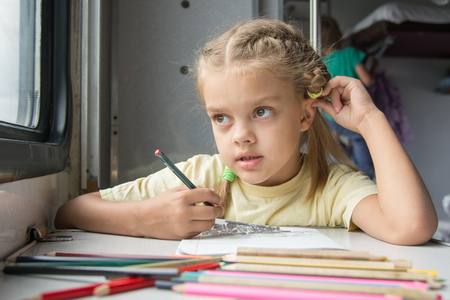 Six year old girl draws a pencil in a notebook for a side table in the second-class train carriage Foto de archivo