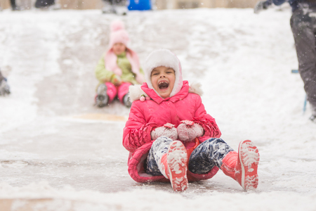 seven year old: Seven year old girl riding a ledyankah winter on a snowy hill surrounded by other children