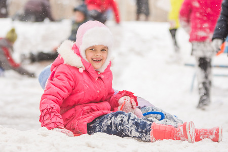 seven year old: Seven year old girl riding winter on a snowy hill surrounded by other children Stock Photo