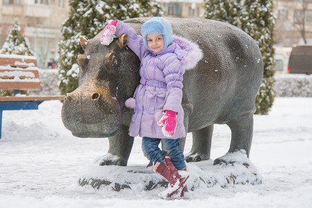 entertainment center: Volgograd, Russia - January 22, 2016: Five-year girl stands the sculpture Hippopotamus sculptor Zurab Tsariteli at the entertainment center Gippopo in Krasnoarmeysk district of Volgograd