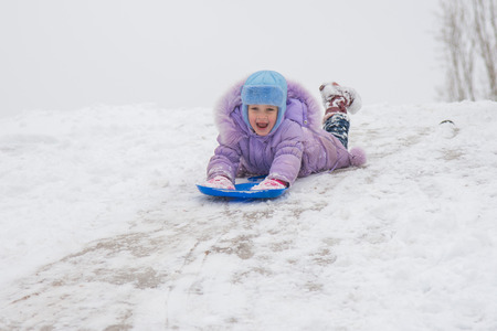 laying forward: Five-year girl riding on a snowy icy hill