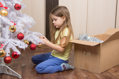 Sad five year old girl takes a toy artificial Christmas tree