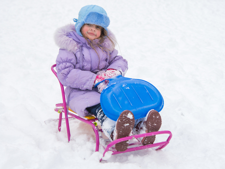returned: disheveled and happy five year old girl sitting on a sled