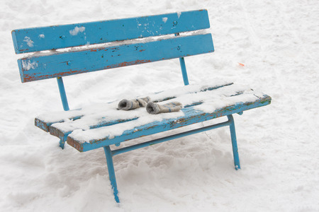 forgotten: winter on a snow-covered bench lie forgotten childrens mittens
