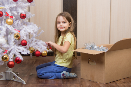 five year old: five year old girl takes fun toys with artificial Christmas tree
