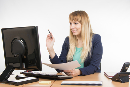 Great: Happy business woman working at a computer and holding a piece of paper and a pen