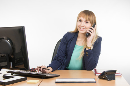 important phone call: Business woman talking on the phone and working on the computer
