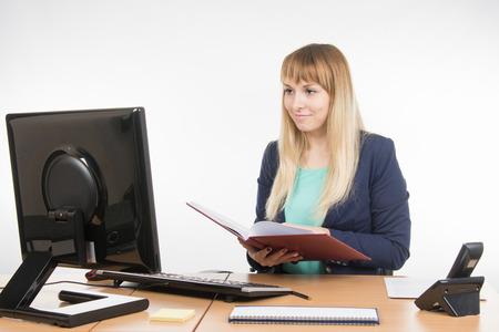 Great: Happy business woman holding a book in the hands of the office and looking at the computer Stock Photo