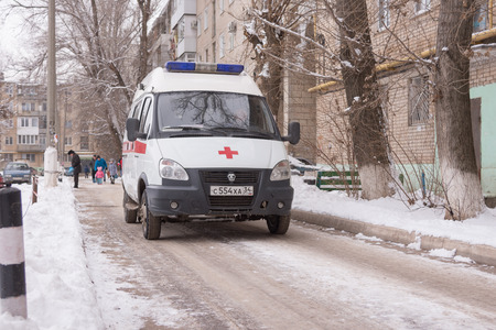 expects: Volgograd, Russia - January 24, 2016: An ambulance stands in the courtyard of a multistory building