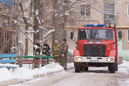 Volgograd, Russia - January 24, 2016: A team of firefighters stand at the entrance of an apartment building, standing next to the car Fire Service of EMERCOM of Russia who came to call on suspicion of fire in high-rise apartment building Redakční