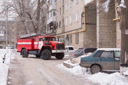 Volgograd, Russia - January 24, 2016: Machine prevents fire service leave many cars parked at the house, who had come to call on suspicion of fire in high-rise apartment building