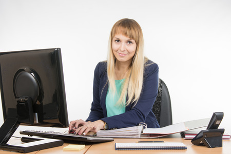 great job: Secretary working in the computer, close the folder with the documents is Stock Photo