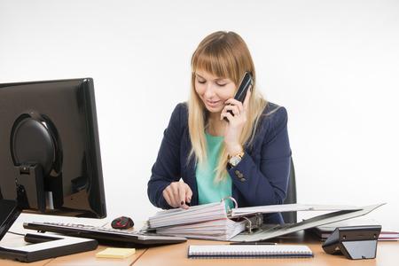La donna d'affari legge il contenuto del documento l'altra parte al telefono Archivio Fotografico