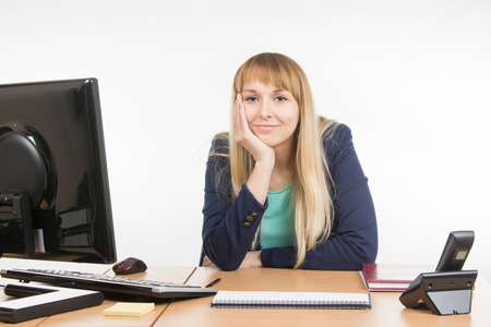 Great: A little bit tired business woman behind a desk Stock Photo